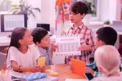 Schooljongen die nieuw tijdschema tonen aan zijn vrienden stock afbeelding