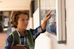 Schooljongen die op noticeboard in de gang richten stock fotografie