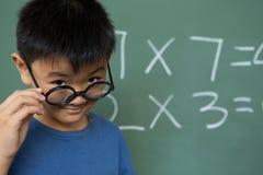 Schooljongen die over schouwspel in een klaslokaal kijken stock foto