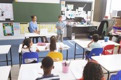 Schooljongen die over windmolen voor zijn klasgenoten verklaren terwijl haar leraar die hem luisteren royalty-vrije stock afbeelding