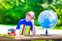 Schooljongen die thuiswerk in schoolwerf doen Stock Fotografie