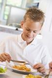 Schooljongen die van zijn lunch in een schoolcafetaria geniet stock foto's