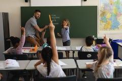 Schooljongen die vinger naar klasgenoten in klaslokaal richten stock foto's