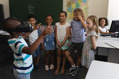 Schooljongen die virtuele werkelijkheidshoofdtelefoon met behulp van terwijl zijn klasgenoten die hem in klaslokaal bekijken royalty-vrije stock afbeelding