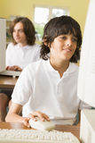 Schooljongen die voor een schoolcomputer bestudeert Royalty-vrije Stock Foto's