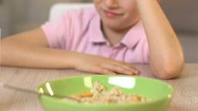 Schooljongen die weigeren havermeel te eten, die afschuw, gezonde voeding voor jonge geitjes voelen stock video