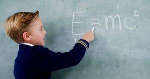 Schooljongen die wiskunde op bord doen stock video