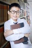 Schooljongen die zich in de bibliotheekdoorgang bevinden Royalty-vrije Stock Foto's