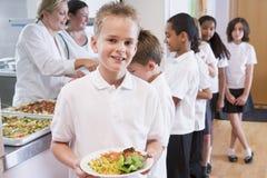 Schooljongen in een schoolcafetaria Stock Fotografie