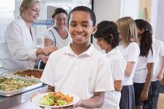 Schooljongen in een schoolcafetaria stock foto's