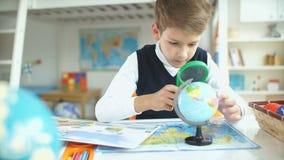 Schooljongen en geografische atlas De jongensstudent die aardrijkskunde bestuderen stock footage