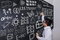 Schooljongen het schrijven wiskundeformule Stock Afbeelding