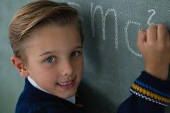 Schooljongen het schrijven wiskundeformule op bord Royalty-vrije Stock Foto's