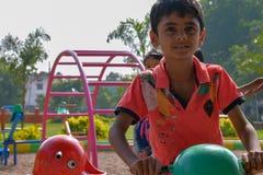 Schooljongen het spelen in het park onder helder zonlicht tijdens vakantie royalty-vrije stock foto