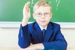 Schooljongen klaar en opgeheven hand omhoog te antwoorden Royalty-vrije Stock Foto's