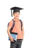 Schooljongen met een holdingsboeken van de graduatiehoed Stock Foto