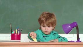 Schooljongen met gelukkige gezichtsuitdrukking dichtbij bureau met schoollevering Onderwijs Concept van de onderwijs het eerste S stock videobeelden