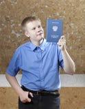 Schooljongen met het certificaat over voltooiing van onderwijs op school royalty-vrije stock afbeelding