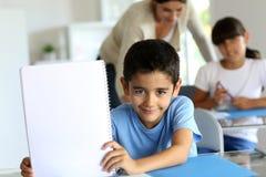 Schooljongen met leeg notitieboekje in klasse Royalty-vrije Stock Foto's