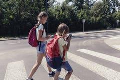Schooljongen met rugzak en zijn tienerzuster die mobiele telefoons bij de voetgangersoversteekplaats met behulp van royalty-vrije stock afbeeldingen