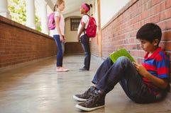 Schooljongen met vrienden op achtergrond bij schoolgang stock afbeelding