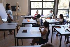 Schooljongen virtuele werkelijkheidshoofdtelefoon met behulp van en zijn klasgenoten en leraar die hem bekijken royalty-vrije stock fotografie