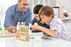 Schooljongens in chemieklasse met leraar stock afbeeldingen