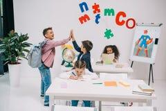 Schooljongens die hoogte vijf geven terwijl schoolmeisjes die in klaslokaal bestuderen Stock Foto's