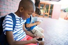 Schooljongens die mobiele telefoons met behulp van bij gang in school stock afbeelding