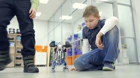 Schooljongens die zelf-gemaakte olifantsrobots maken bij het laboratorium van de techniekschool stock footage