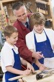 Schooljongens en leraar in houtbewerkingsklasse Stock Fotografie