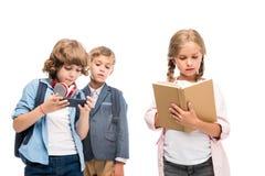 Schooljongens met smartphone en schoolmeisje met boek Stock Afbeeldingen