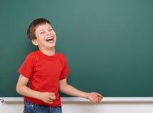 Schooljongenspel en lach dichtbij een bord, lege ruimte, onderwijsconcept royalty-vrije stock afbeelding