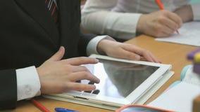 Schooljongenspelen in spelen die computertablet gebruiken stock video