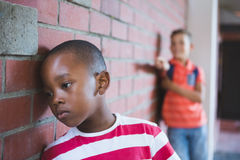 Schoolkid bullying a sad boy in corridor Royalty Free Stock Photos
