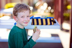 Schoolkid eating lunch. Beautiful positive schoolboy enjoying healthy lunch during recess outdoor Stock Images