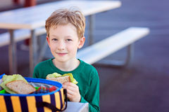 Schoolkid eating lunch. Beautiful positive schoolboy enjoying healthy lunch during recess outdoor Royalty Free Stock Photos
