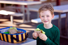 Schoolkid eating lunch. Beautiful positive schoolboy enjoying healthy lunch during recess outdoor Royalty Free Stock Photo