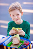 Schoolkid eating lunch. Beautiful positive schoolboy enjoying healthy lunch during recess outdoor Royalty Free Stock Image