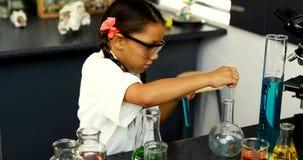Schoolkid egzamininuje substancję chemiczną w laboratorium 4k zbiory wideo