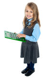 Schoolkid pressing key 5 on big green calculator. Sweet smiling kid in uniform using big green calculator Stock Photo