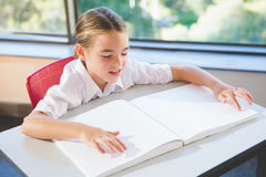 Schoolkid reading braille book in classroom stock photo