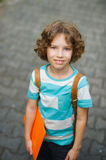 The schoolkid stand on a schoolyard and smiles. The boy has a nice face, a fair hair, an open look. It has behind shoulders a satchel. Orange folder in hands Royalty Free Stock Image