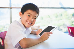 Schoolkid using digital tablet in classroom. Close-up of schoolkid using digital tablet in classroom at school Stock Photos