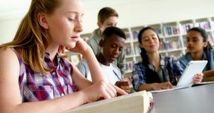 Schoolkids που μελετά στη βιβλιοθήκη 4k απόθεμα βίντεο