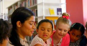 Schoolkids азиатской учительницы уча в школьной библиотеке 4k акции видеоматериалы