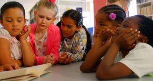 Schoolkids азиатской учительницы уча в школьной библиотеке 4k видеоматериал
