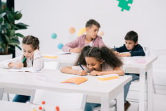 Schoolkids писать в ученических книгах и изучая совместно в классе Стоковое Фото