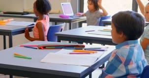Schoolkids поднимая руку пока сидящ на столе в начальной школе 4k акции видеоматериалы