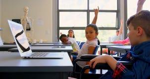 Schoolkids поднимая руку пока сидящ на столе в начальной школе 4k видеоматериал